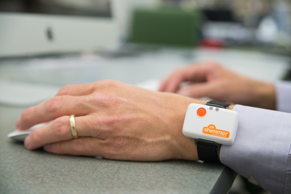 photo of Shimmer device on a wrist, wherein the hand is using a mouse and the other hand is using a keyboard